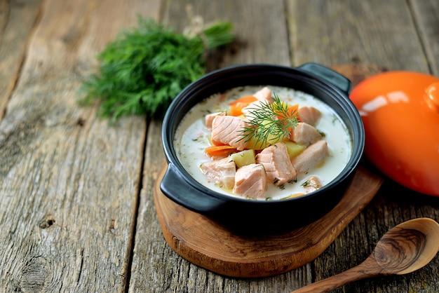 Суп из лосося со сливками на старом деревянном фоне