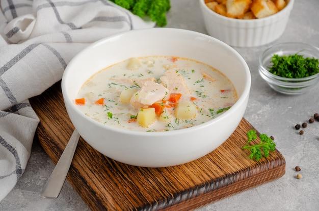 Суп из лосося со сливками, картофелем, морковью, зеленью и гренками в миске на сером фоне бетона.