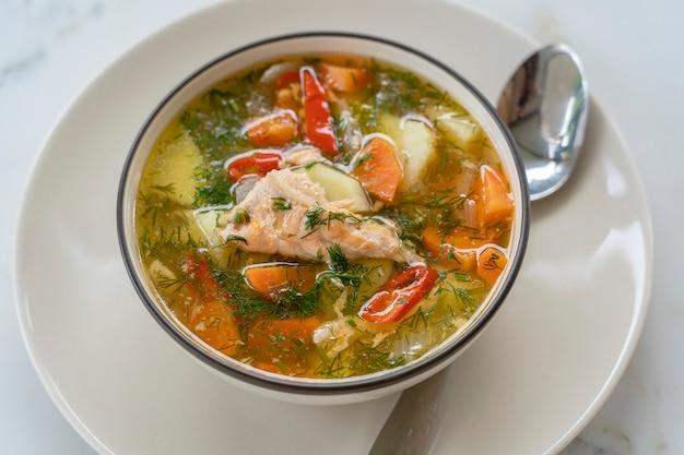 Суп из лосося с картофелем, морковью, укропом, перцем в миске, крупным планом
