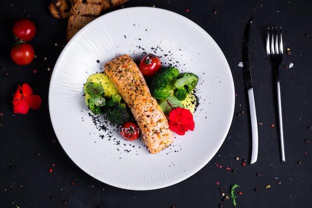 サーモンステーキ、揚げブロッコリー、焼きチェリートマトとクリームソースを組み合わせた、暗い表面