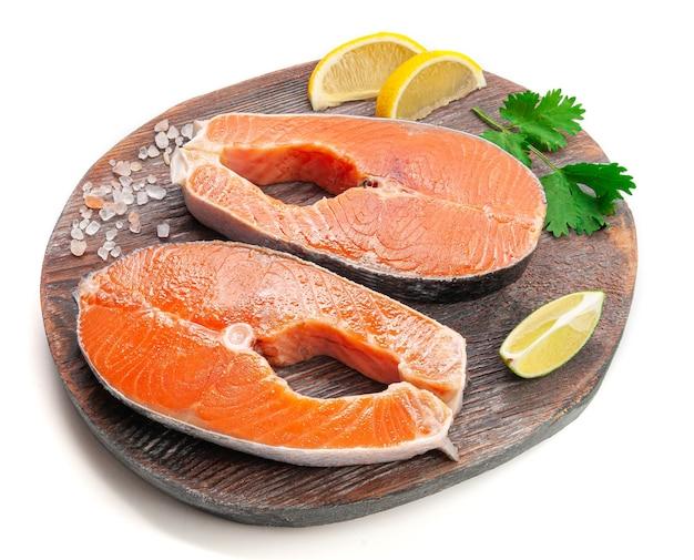 Стейк из лосося. украшается дольками лимона, кинзой и солью. на деревянной доске. белый фон. изолированный. крупный план.