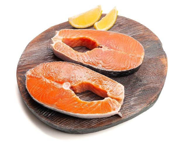 Стейк из лосося. украшен дольками лимона. на деревянной доске. белый фон. изолированный. крупный план.