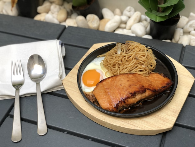 Salmon steak grilled with fried egg and spaghetti noodles pepper onion on hot pan and wood plate
