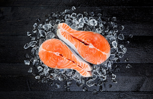 Salmon steak on ice on black wooden table top view