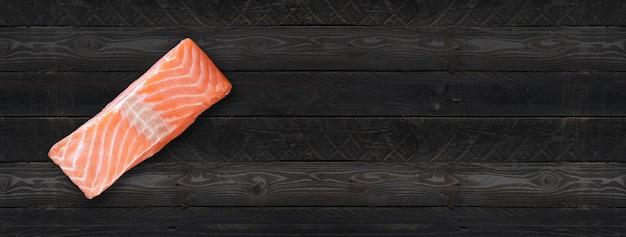 Стейк из лосося, изолированные на фоне черной деревянной доске. вид сверху. горизонтальный баннер