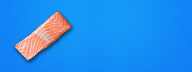 파란색 배경에 격리된 연어 스테이크입니다. 평면도. 가로 배너