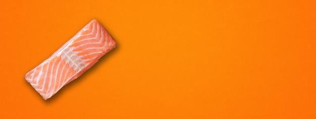 オレンジ色の背景に分離されたサーモンステーキ。上面図。横バナー