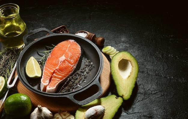 暗い背景に具材を使って揚げるサーモンステーキ