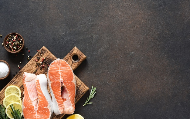 Salmon steak raw fish with spices prepared for cooking on a wooden board on a dark concrete background.