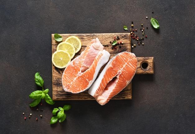 暗いコンクリートの背景に木の板で調理するために準備されたスパイスとサーモンステーキ生の魚。