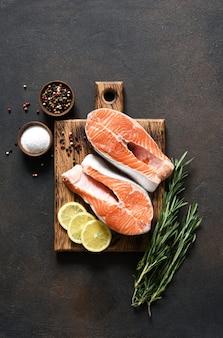 어두운 콘크리트 배경에 나무 보드에 요리를 위해 준비하는 향신료와 연어 스테이크 생선.