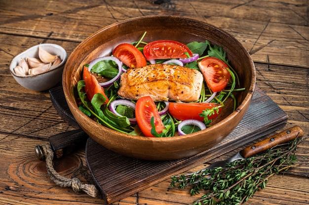 나무 접시에 녹색 잎 arugula, 아보카도, 토마토와 연어 스테이크 샐러드. 나무 배경입니다. 평면도.