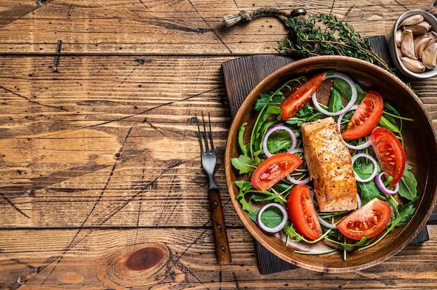 나무 접시에 녹색 잎 arugula, 아보카도, 토마토와 연어 스테이크 샐러드