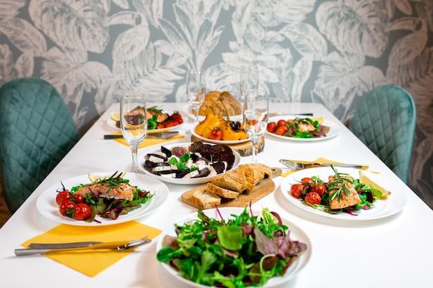 ルッコラと野菜のサーモンステーキ。人とのごちそう。食物と一緒に美しい缶詰の白いテーブル。お祝いディナー。テーブルで家族。昼食