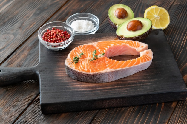 Salmon steak with avocado and seasonings on the wooden board