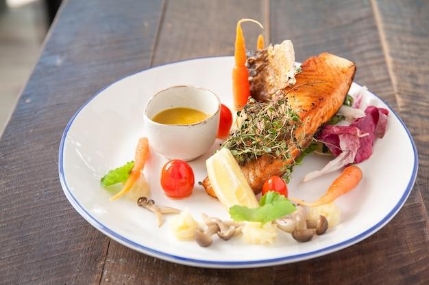 Стейк из лосося с соусом и салатом