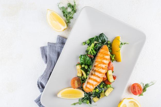Стейк из лосося со свежими овощами и дольками лимона на белой тарелке с салфеткой на светлом фоне. вид сверху с копией пространства для текста. ресторанная еда. горизонтальная ориентация.