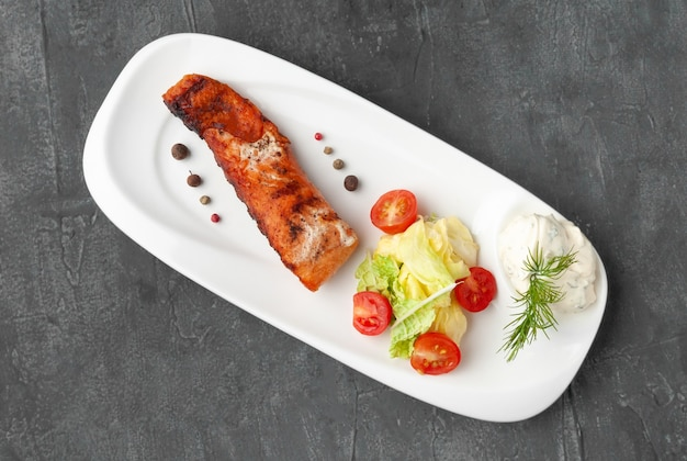 Salmon steak with fresh vegetables and tzatziki sauce. on a white plate. view from above. on a gray concrete background.