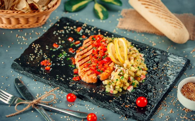 Salmon steak with lemon and vegetable salad on a black stone platter.