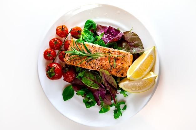 レタス、チェリートマト、レモンスライスのサーモンステーキ。祝賀会。昼食用の食べ物。赤い魚のグリル。オーブンで焼き鮭