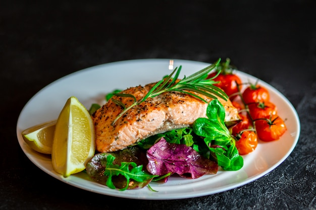 Salmon steak with lettuce, cherry tomatoes and lemon slices. gala dinner. food for lunch. grilled red fish. baked salmon in the oven