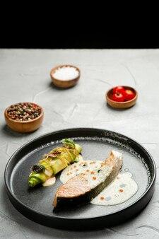 세라믹 접시에 소스를 곁들인 연어 스테이크. 호박 롤과 재료를 콘크리트 테이블에 얹은 구운 연어