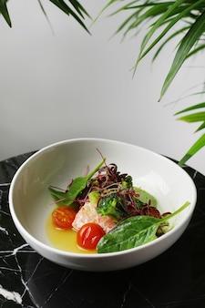 Whute 접시와 대리석 테이블 근접 촬영에 시금치를 곁들인 연어 스테이크.
