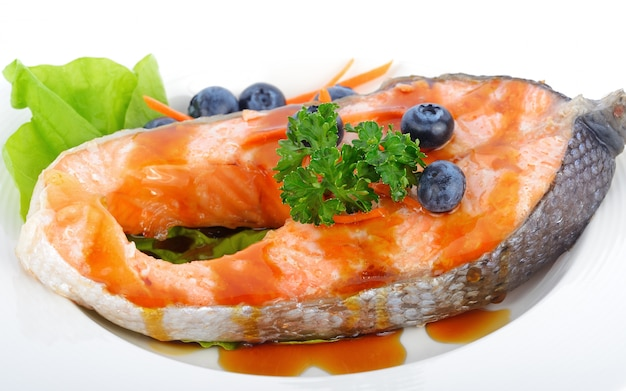 Salmon steak with vegetables and fruit.