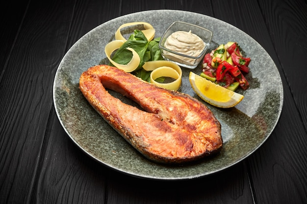 Salmon steak with vegetables, lemon and sauce on black
