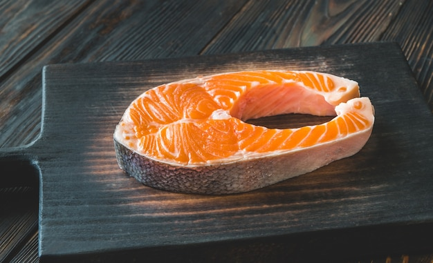 Salmon steak on the wooden board close-up