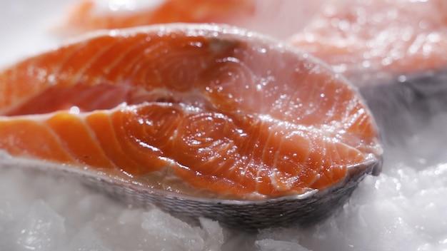 サーモンステーキとサーモンフィレ新鮮なサーモンステーキとフィレを氷の上に並べる Premium写真