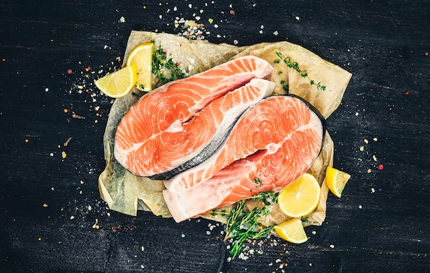 Salmon steaks on black, top view, photo filtered in vintage style