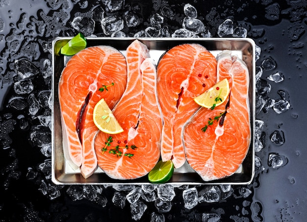 Salmon steaks on ice on black