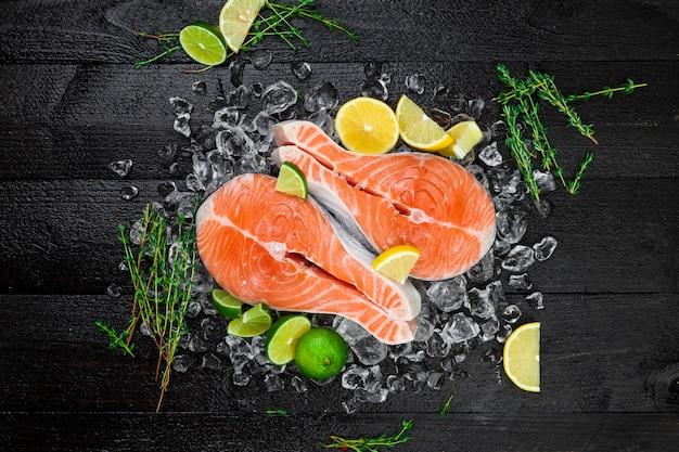 Стейки лосося на черной деревянной поверхности Premium Фотографии