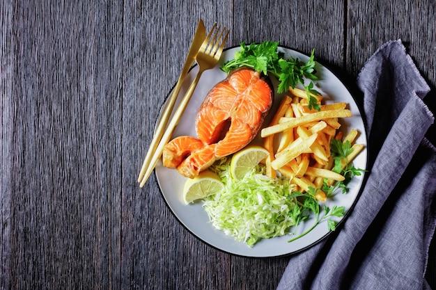 Стейки из лосося подаются с картофелем фри и салатом из капусты на тарелке на темном деревянном столе, горизонтальный вид сверху, плоская планировка, свободное пространство