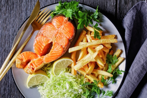 Стейки из лосося подаются с картофелем фри и салатом из капусты на тарелке на темном деревянном столе, горизонтальный вид сверху, плоская планировка