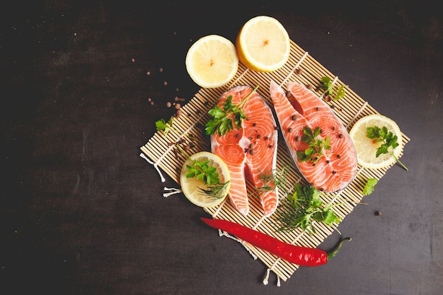 Salmon steaks with lemon and spices on black background
