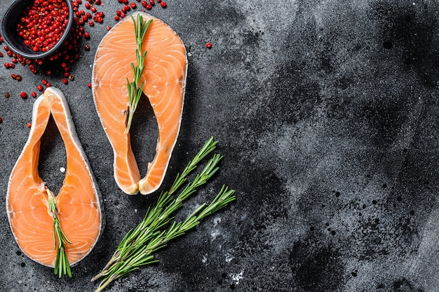 ローズマリーとピンクペッパーのサーモンステーキ。生の有機魚。黒の背景。上面図。スペースをコピーします。
