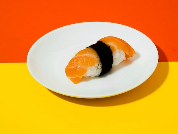 노란색과 주황색 배경에 흰색 접시에 연어 초밥