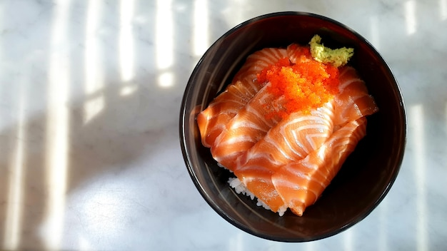 Salmon sushi rice ja panese food in a bowl on the table and copy space
