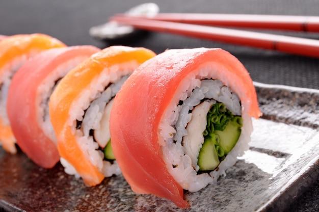 Rotolo di sushi di salmone con bacchette closeup