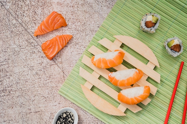 Salmon sushi rolls on circular wooden plate on green placemat with chopsticks and sesame seeds