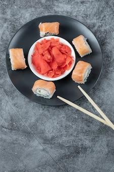 Rotoli di sushi di color salmone serviti con zenzero rosso su un piatto nero.