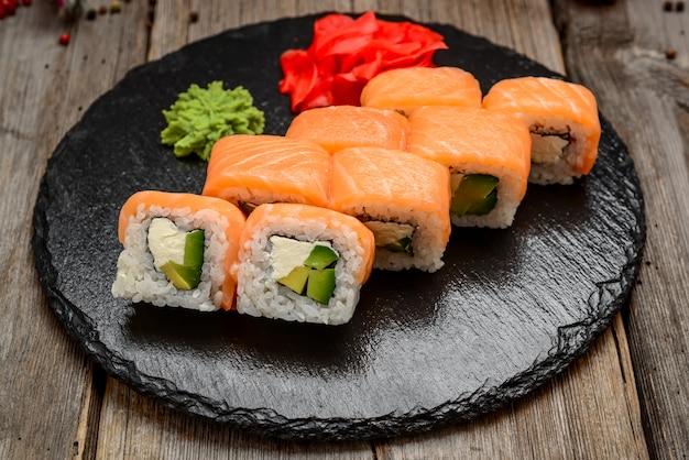 Salmon sushi rolls on stone board