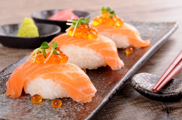 Salmon sushi with caviar and chopsticks