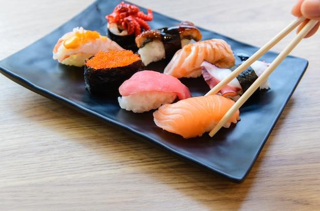 Salmon sushi with chopstick and nigiri sushi set on clay plates