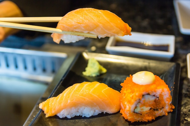 Salmon sushi with chopsticks and fresh japanese sushi rolls over black background