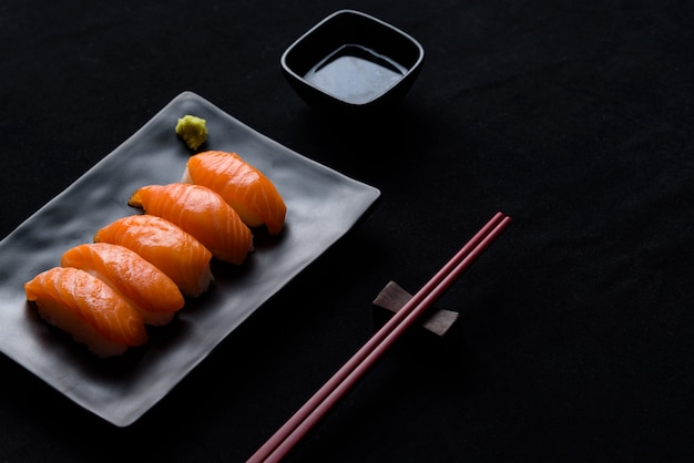 Salmon sushi with green wasabi on black plate or dish and shoyu sauce on black background