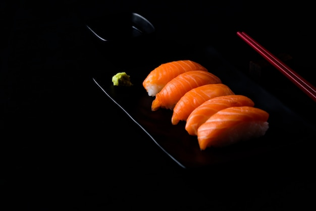 Salmon sushi with green wasabi on black plate or dish and shoyu sauce