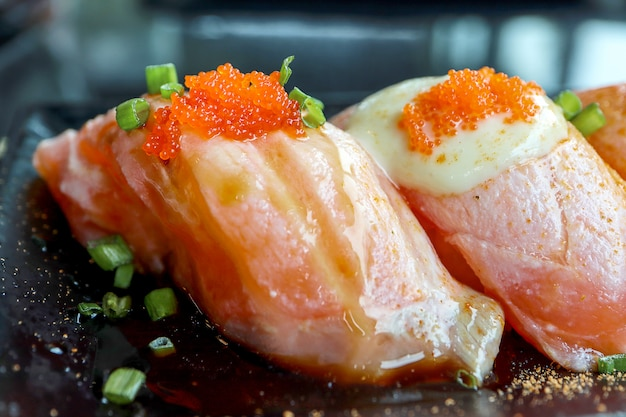 Salmon sushi with tobiko eggs on top in black plate.